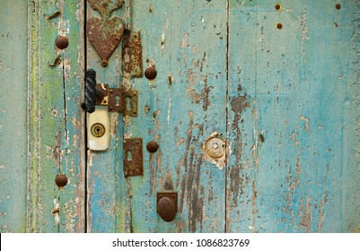 Ancient wooden door, painted in teal (blue greenish) color. Damaged by time and weather. With many rusted keyholes and locks. French countryside.