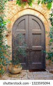 Ancient wooden entrance doors with rustic metal nails, surrounded by plants, Old Jaffa quarter (Yafo, Yaffa), Tel Aviv
