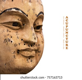 Ancient wooden face showing acupuncture points, isolated on white background (Translation: the characters on the face are names of each acupuncture point)