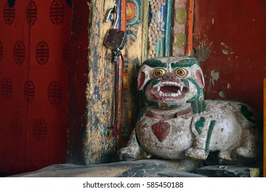 Ancient wooden figure of a traditional Tibetan snow lion at the door in the Buddhist Hemis Monastery, Himalayas, India.