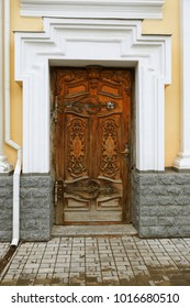 An ancient wooden front door decorated with wood carvings. The historical style of the facade of the Catholic Polish church. Beautiful vintage carved rich front door