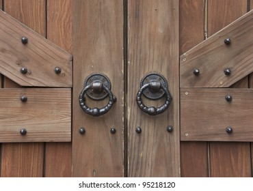 ancient wooden gate with two door knocker rings close-up