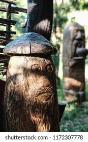 Ancient wooden idols of the Slavic gods. Two wooden idols of different gods of ancient Slavs. Faces are carved on idols. Close-up highlighted the first idol. The background is blurred.