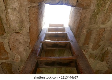 Ancient wooden ladder, viewed from below, climbing up to the skylight through a small square opening in a historic structure