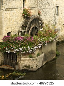 An ancient wooden mill wheel and small canal in the old part of Bayeux, France.  The area around the wheel is decorated with flowers, and the old stone buildings  have interesting textures.