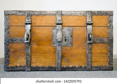 Ancient wooden trunk front with padlock hasps and engraving. Antique loot box.