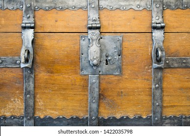 Ancient wooden trunk front with padlock hasps and engraving. Antique loot box. Isolated. Close up.