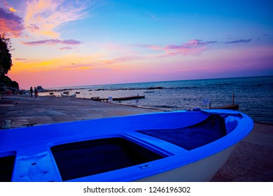"""Ancona, Italy 24 July 2018: Blue boat in the foreground with pink sunset behind the characteristic city """"Passetto"""" with people sunbathing at the beach"""