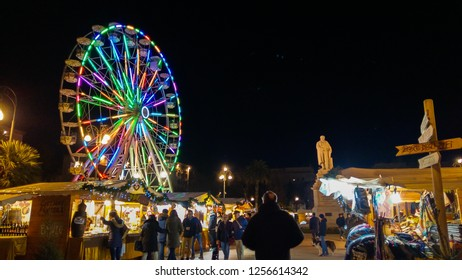 ANCONA, ITALY - DECEMBER 12, 2018: Piazza Cavour with christmas market and colored ferris wheel in the center of Ancona at night, Marche, Italy