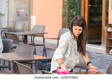 Ancona, Italy - September 23th, 2018: A female waitress wiping and cleaning a table working at a coffee shop outdoors in Ancona, Italy.