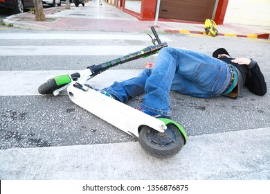 Málaga, Andalusia, Spain February 26. 2019 - Young man is lying injured on a crosswalk just after an accident in the street with an electric scooter lime patinete
