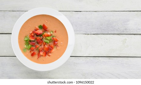 Andalusian gazpacho served in a white plate on a wooden table. Top view and empty copy space for Editor's text.