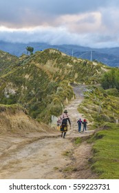 Andean mother with his children walking to dirty path at border of Quilotoa crater, Latacunga, Ecuador