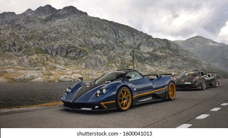 Andermatt, Switzerland - August 2019: two Italian Pagani supercars, blue Zonda Unica, and black with orange Huayra Dragon Imola, attending annual Supercar Owners Circle rally held at Swiss Alps.