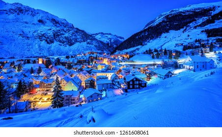 Andermatt village in swiss Alps mountains, snow covered in winter in blue evening light, panoramic view, Uri, Switzerland