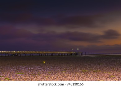 The Andernos France pier by night and low tide.