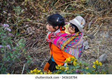 THE ANDES, PERU - MAY 30, 2012: Quechua mother with child in a village in the mountains of The Andes over Ollantaytambo, Peru