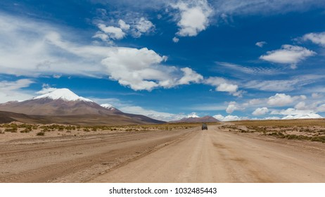 Andes region, Bolivia with snow covered volcano and offroad cars passing the waste land