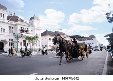 Andong is typical transportation in Jogjakarta city, with the background historycal building