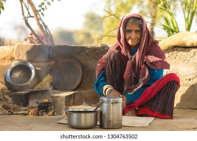 Andoure, India - December 21, 2017: indian woman cooking chapatis at outdoor kitchen of there house, Chapatis are the staple diet of all Indians, Andoure, India - December 21, 2017