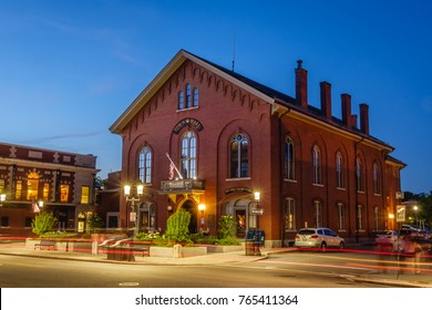 Andover, MA, USA-June 08, 2016. Night scene of Andover's historic Old Town Hall building with traffic light trails on Main Street.