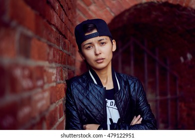 Androgynous close up portrait of asian girl in black cap and coat. Thoughtful expression emotion. Red brick wall background.