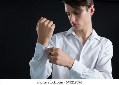 Androgynous man adjusting his hand cuffs