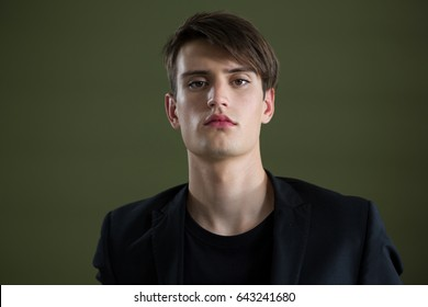 Androgynous man looking at camera against green background