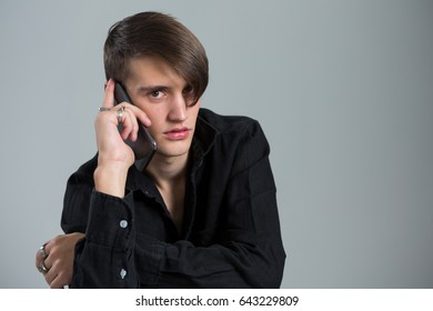Androgynous man talking on his mobile phone against grey background