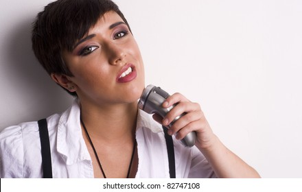 Androgynous woman shaving her face with battery operated shaver