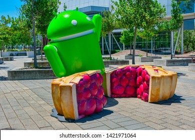Android Pie sculpture near Googleplex in Silicon Valley. Bugdroid standing in between a piece of pie that has been pulled from a full cherrie pie - Mountain View,California, USA - June 11, 2019