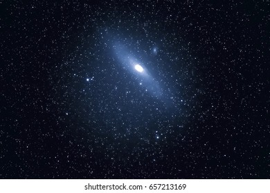The Andromeda Galaxy surrounded by stars in a black sky.
