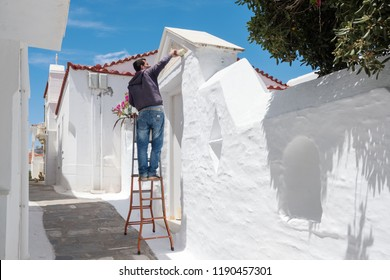 Andros, Greece - May 31, 2018: Unidentified greek man paints wall in traditional cycladic white color on Andros island, Cyclades, Greece