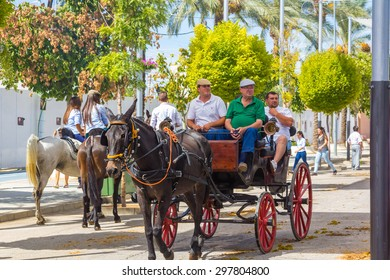 ANDUJAR,SPAIN - September, 6: Participants in the fair of the horse walk on their carriages Andalusian style and typical costume on September, 6, 2014 in Andujar, Spain