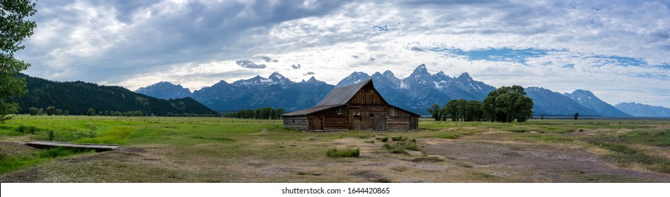 andy chambers residence old mormon barn farm in summer with blue colored grand tetons in background. panoramic, panorama