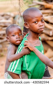 ANEHO, TOGO - MARCH 6, 2012: Unidentified Togolese boy carries his little baby brother on his back in Togo, Mar 6, 2012. Children in Togo suffer of poverty due to unstable economical situation