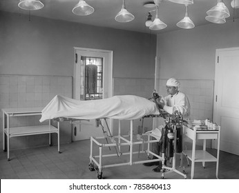 Anesthesiologist administers ether and nitrous oxide to patient before surgery in operating room. 1922 in a hospital in Washington, D.C.