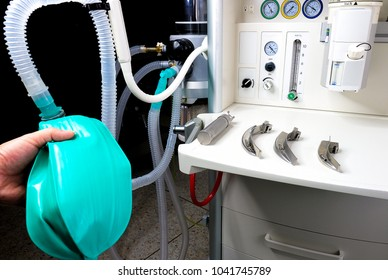 an anesthesiologist with an anesthetic machine in the operation room with a laryngoscope and a set of blades ready for intubation