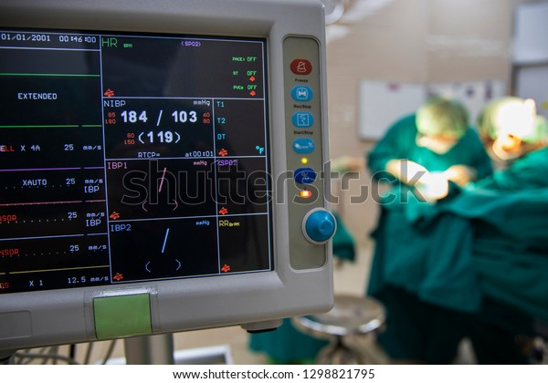 Anesthetic monitor shown high blood pressure  in the operating room with surgeon doing surgery in blurred background. Monitor screen use for patient safety during procedure. Medical concept.