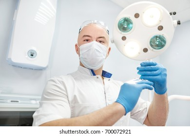An anesthetist doctor holds a syringe in his hands and looks into the frame