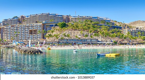 Anfi beach with palm trees and turquoise bay / Gran Canaria in Spain