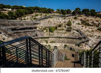 Anfiteatro Romano di Cagliari/ Roman amphitheatre of Cagliari ruins on a sunny day with blue sky. Nobody in the scene. View with stairs heading down.