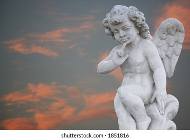 Angel boy statue on orange sky