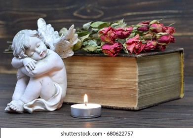 Angel, candle and dry flowers on wooden background