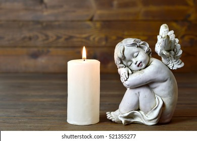 Angel and candle on wooden background