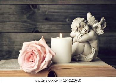 Angel, candle and pink rose on wooden background