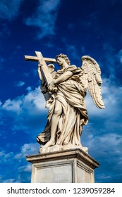 Angel with the cross on the Ponte Sant'Angelo over the Tiber, at the Mausoleum of Roman Emperor Hadrian, usually known as Castel Sant'Angelo, in Rome, near the Vatican. Italy