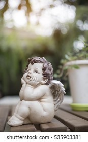 Angel or cupid figure with the green background with sun lighting