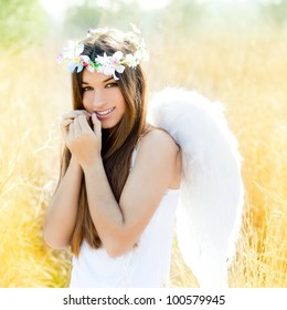 Angel ethnic woman in golden field with feather white wings and flowers crown