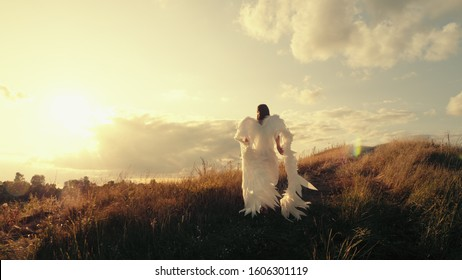 Angel goes to the top of the hill. Brunette girl in a white dress with angel wings goes to the top of the hill at sunset